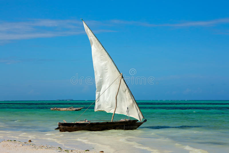 Wooden sailboat on the beach. Wooden sailboat (dhow) on a tropical beach of Zanzibar island stock image