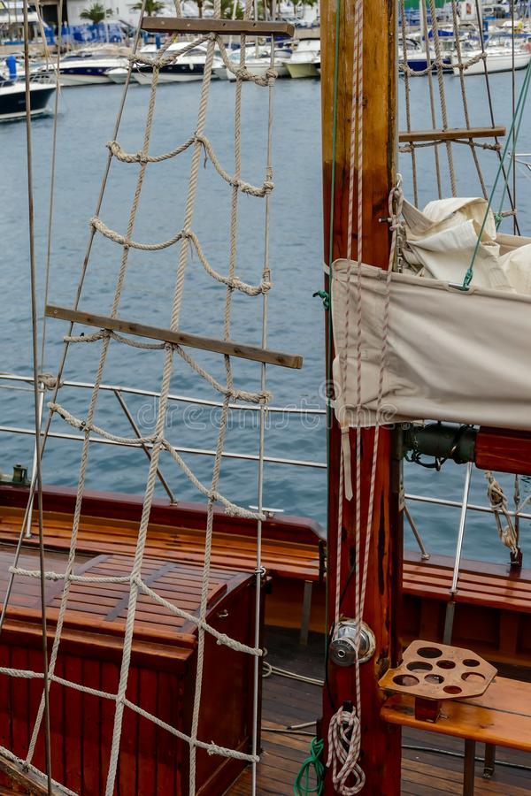 Wooden sailboat on the blue mediterranean sea Details of a classic beautiful sailing yacht with ropes knots and wood plank on deck. Wooden sailboat on the blue royalty free stock images