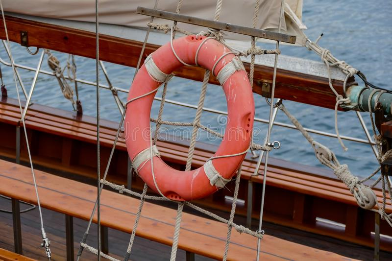 Wooden sailboat on the blue mediterranean sea Details of a classic beautiful sailing yacht with ropes knots and wood plank on deck. Wooden sailboat on the blue stock photo