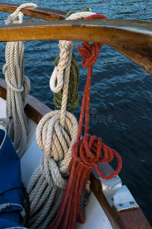 Wooden sailboat on the blue mediterranean sea. ropes, knots and wood plank on deck background. Wooden sailboat on the blue mediterranean sea. Details of a stock image