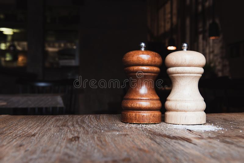 Wooden salt and pepper mills on a wooden table. royalty free stock photo