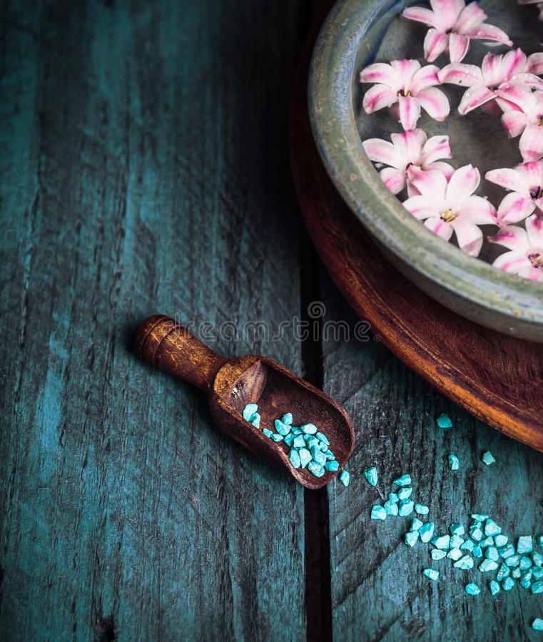 Wooden scoop with blue sea salt and bowl with water and flowers royalty free stock photos
