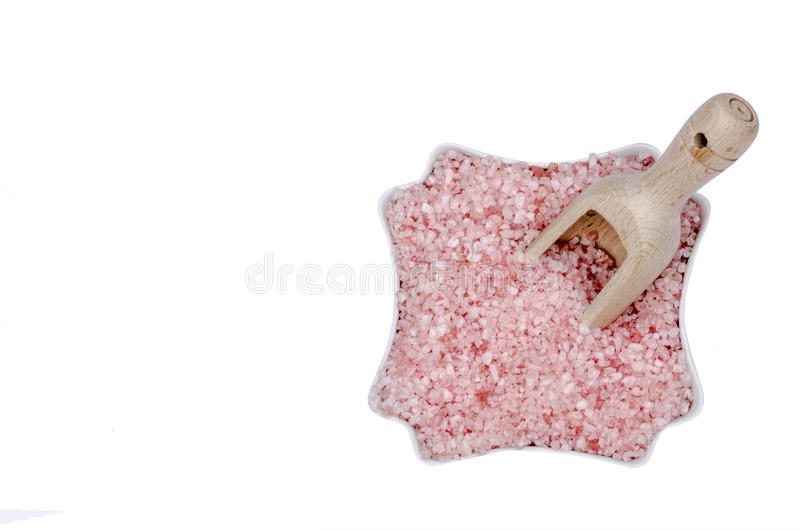 Wooden scoop, bowl full of bath salts with pink and white grains stock photography