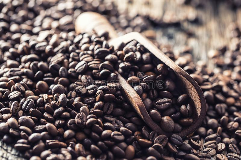 Wooden scoop full of coffee beans on old oak table stock photography