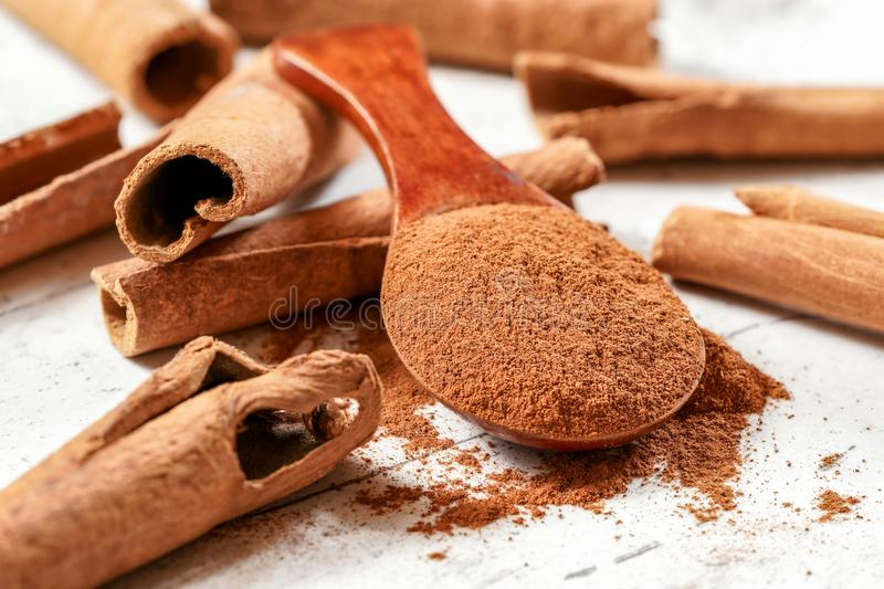 Wooden scoop with ground cinnamon powder, whole bark sticks in background on white baord royalty free stock images
