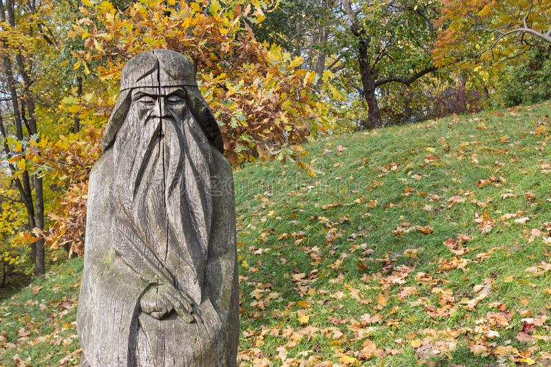 Wooden sculpture of old man with a long beard. Wooden sculpture of a long bearded old man with feather pen in his hand, green grass and forest as a background stock image