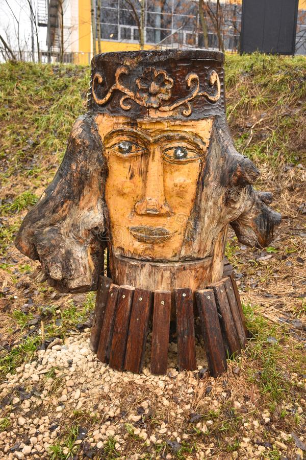 Wooden sculpture in park in shape of woman`s face stock photo