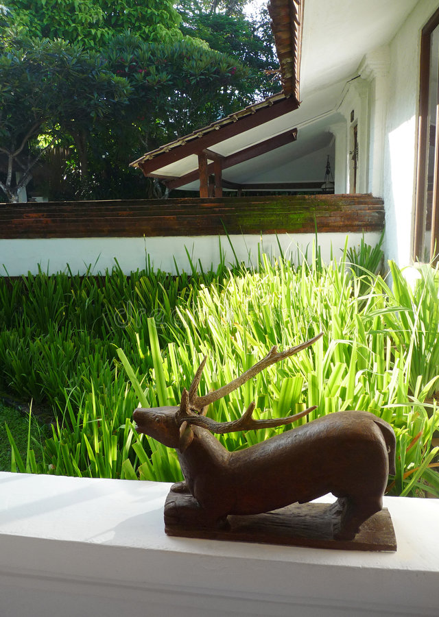 Wooden sculpture on patio. An image showing an ornamental antique wood carving of a deer, placed as decor piece on the ledge of a veranda, patio area or porch royalty free stock photo