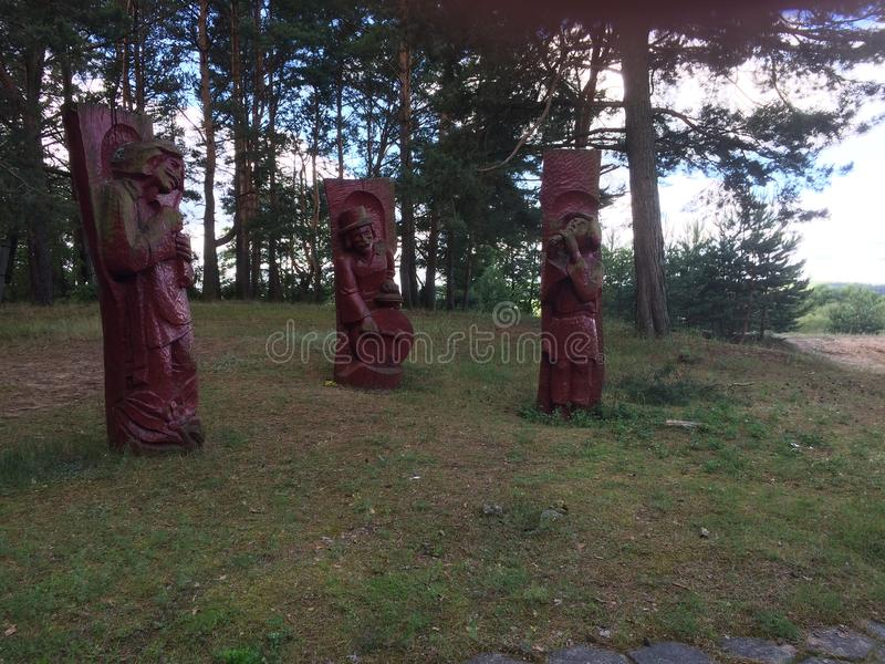 Wooden sculptures in the summer forest stock photos
