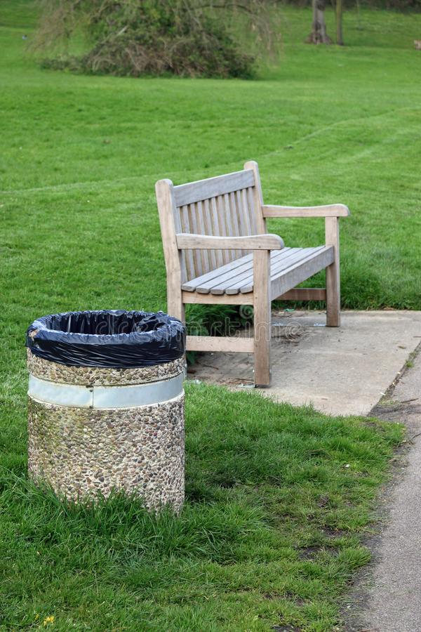Wooden seat with concrete litter bin. Wooden park seat on a concrete plinth with an adjacent concrete litter bin containing a black plastic bin liner with grass royalty free stock image