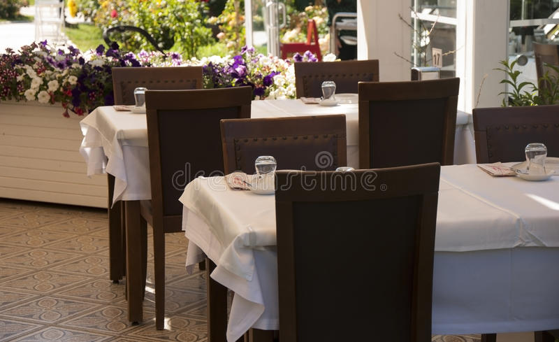 Wooden served tables in turkish restaurant, Izmir province,Turk. A few tables in turkish restaurant are waiting for visitors.Small tea glasses can be seen on the stock photography