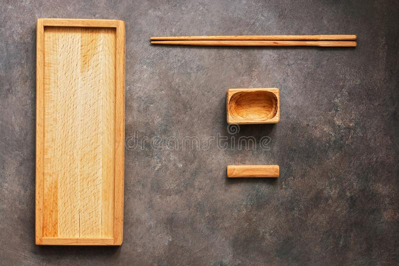 A wooden set of dishes and cutlery Asian cuisine sushi and rolls, a rectangular plate, chopsticks and a bowl for soy sauce on a. Dark background. Top view, flat stock image