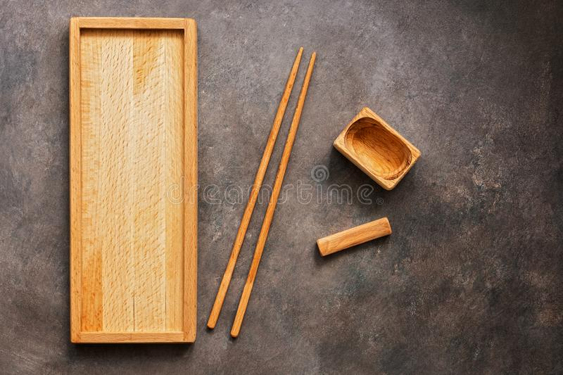 A wooden set of dishes and cutlery Asian cuisine sushi and rolls, a rectangular plate, chopsticks and a bowl for soy sauce on a. Dark background. Top view, flat royalty free stock photography