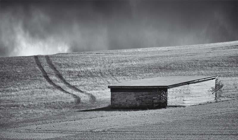 Wooden shed in a field with vehicle tracks leading towards the horizon with ominous dark clouds in the distance. Wooden shed in a field with vehicle tracks stock photography