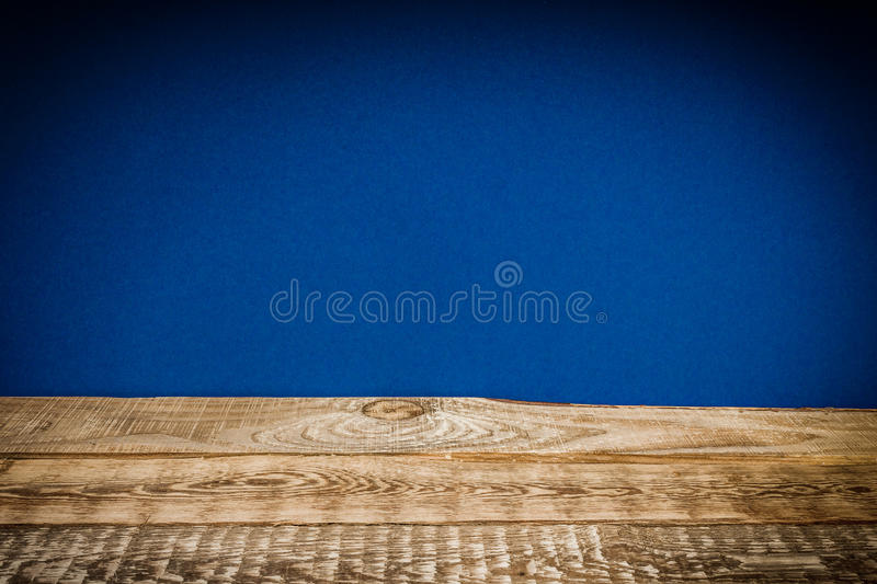 Wooden shelf and blue wall. Old and wooden shelf and dark blue wall stock image
