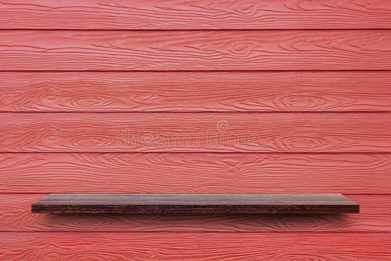 Wooden shelf on the red synthetic wood wall. royalty free stock photo