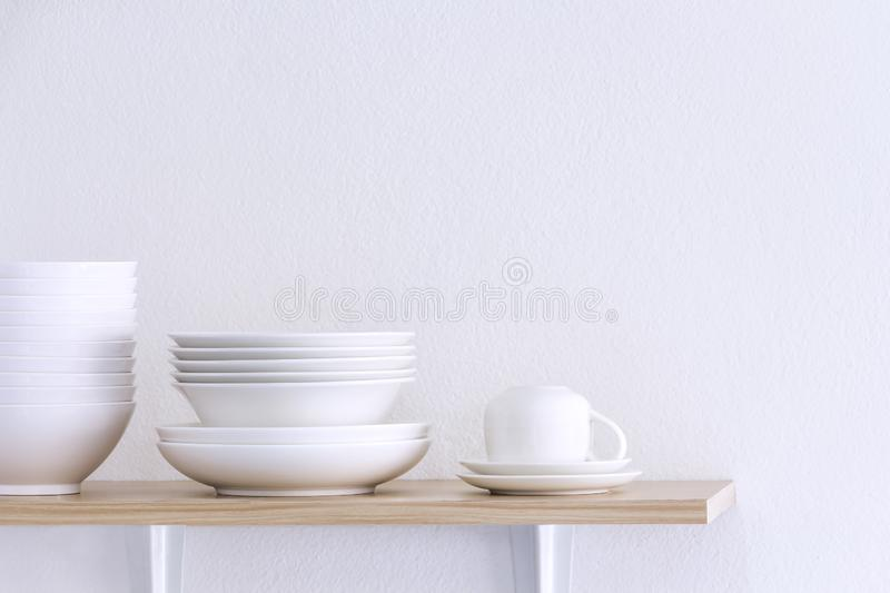 Wooden shelf template isolated on white wall background which on set stacked white bowls and plates as items tableware for. Decorated interior or montage of royalty free stock photo