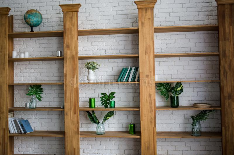Wooden shelving with flowers and books in room. Wooden shelving with flowers and books in the room royalty free stock photos