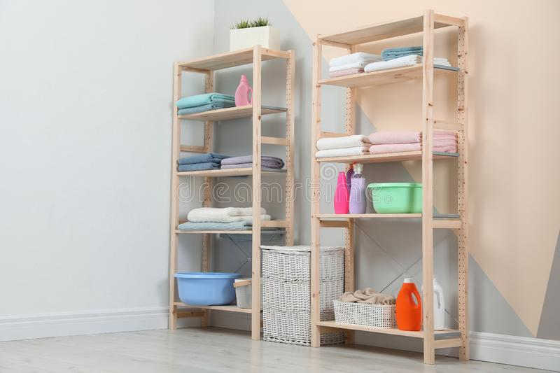 Wooden shelving units with clean towels and detergents in room interior royalty free stock photo