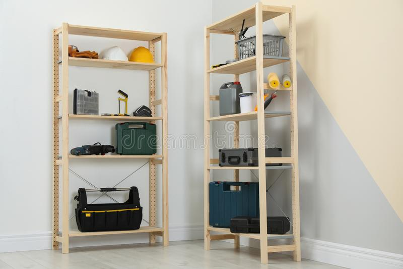 Wooden shelving units with different instruments near color wall royalty free stock image