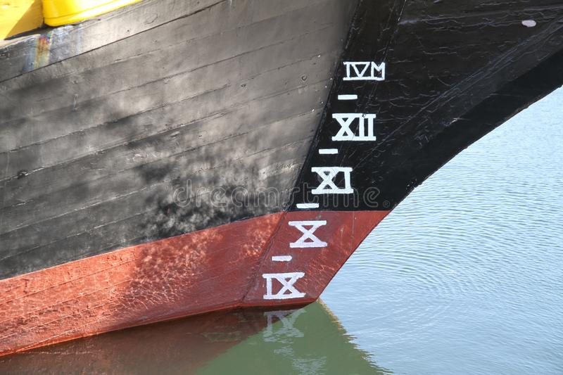 Wooden ships plimsoll lines with water reflections in sunlight. Black painted hull with white painted markings royalty free stock photos