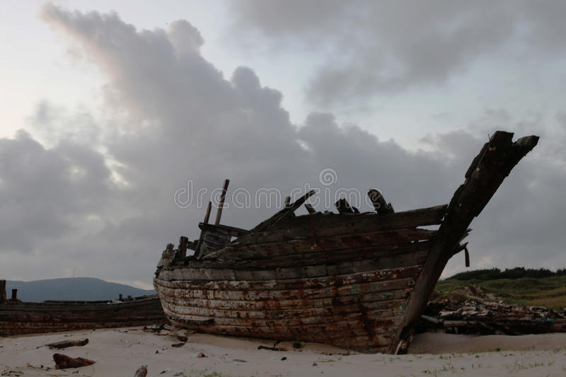 Wooden shipwreck. The large wooden shipwreck lay on the beach by the sea of China after his long journey in storms stock image