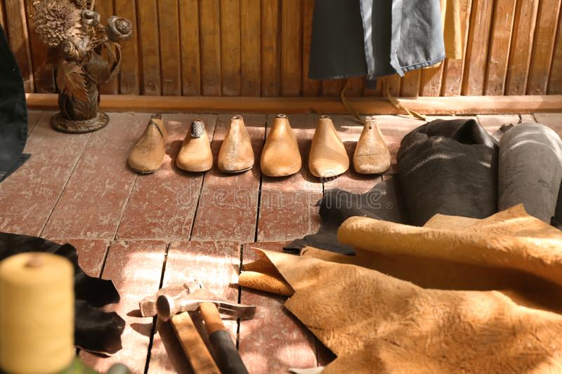 Wooden shoe-trees with craft tools and leather on floor in workshop royalty free stock photography