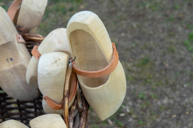 Wooden shoes in Dutch style lying in a basket of wickerwork. Lifestyle stock photography