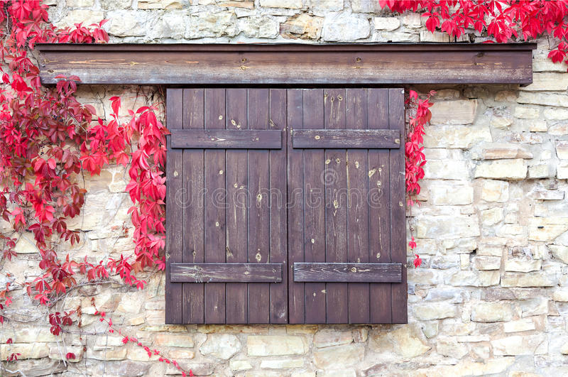 Wooden shutters on stone wall background with autumn leaves stock photos