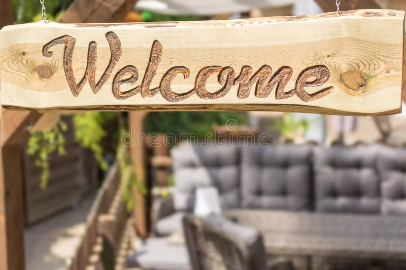 Cozy garden with modern sitting area in rattan design and wooden welcome sign royalty free stock photo
