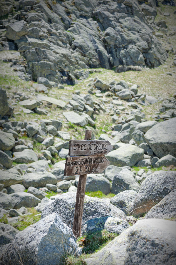 Wooden sign on mountain road in foreground royalty free stock photo