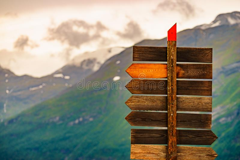 Wooden sign in norwegian mountains. Tourism vacation and travel. Wooden signpost in norwegian mountains. Rainy cloudy weather stock photos