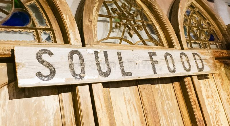A Wooden Sign that says Soul Food. A wooden sign on ornamental doors with the words Soul Food royalty free stock photos
