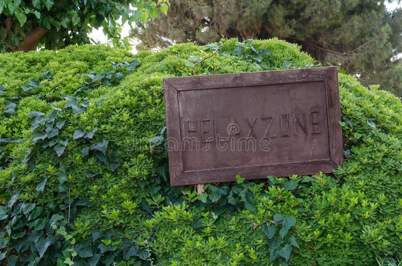 Wooden sign Relax Zone on big green bush on the park.  stock photography