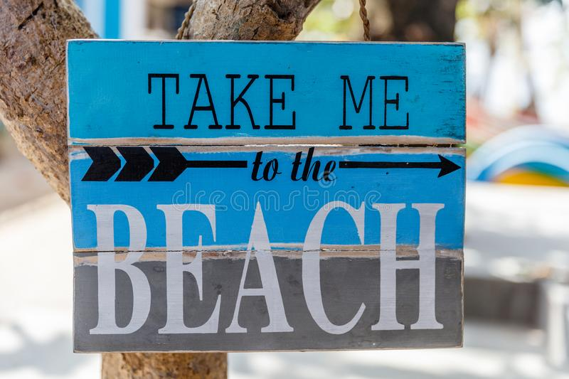 Wooden sign TAKE ME TO THE BEACH with an arrow on a tree at Pantai Sanur, Bali, Indonesia royalty free stock photography