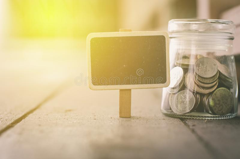 Wooden signage and coin in jar .fade color effect wooden background with light effect royalty free stock image