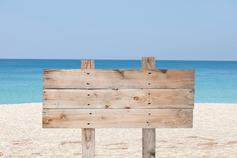 Wooden signboard on blue sky and on tropical beach for summer ba. Ckground stock image