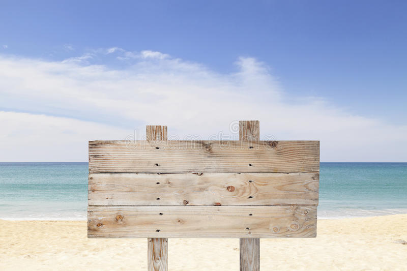 Wooden signboard on blue sky and on tropical beach for summer ba. Ckground royalty free stock photo