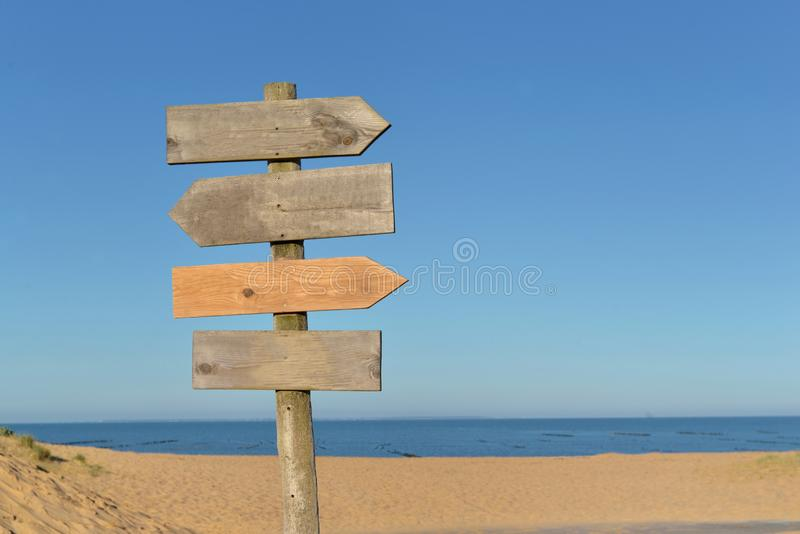 Wooden signs on a post in frint of a beach stock image