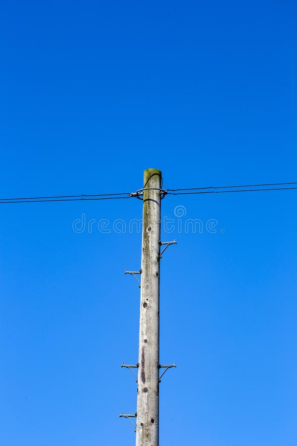 Pole with over head telephone wire against deep blue sk. Wooden single pole with overhead telephone wire and climbing tools for the engineer royalty free stock image