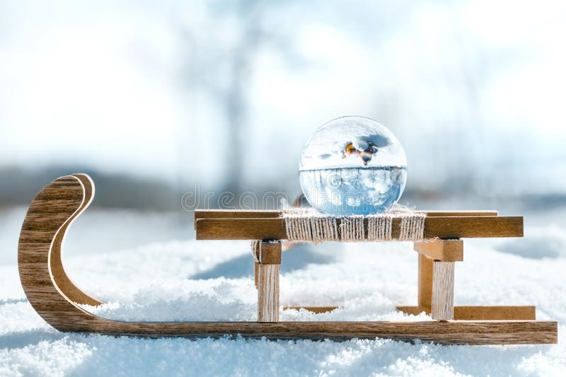 Wooden sledge with a crystal or glass ball, winter landscape reflection with christmas balls stock photo