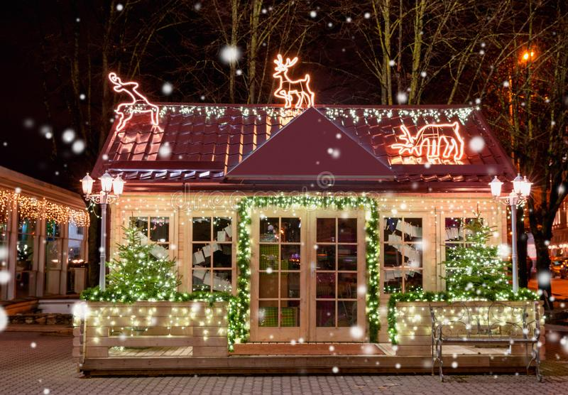Wooden small house with New Year decoration in the night. Christmas background. Christmas window. Christmas tree outside. The window. Riga. Latvia stock photography
