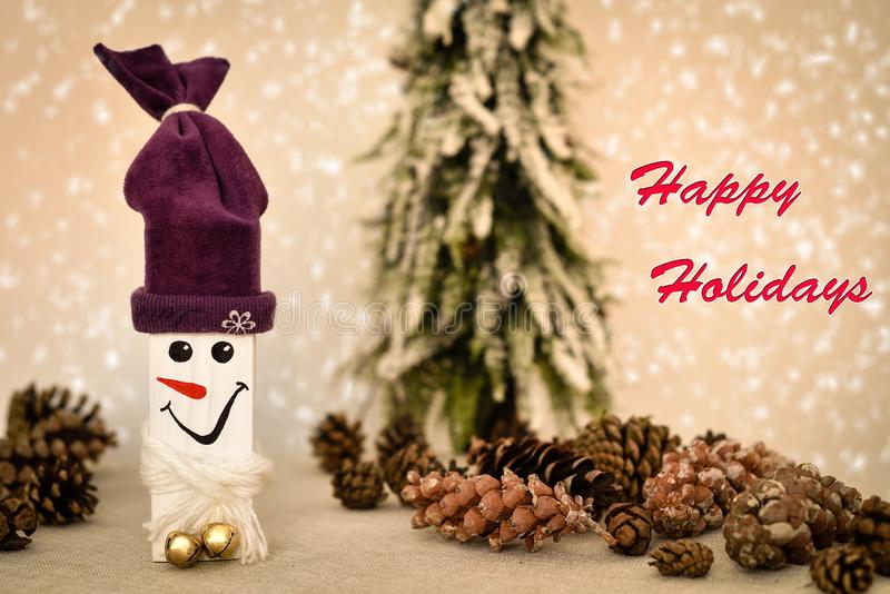 Wooden snowman and pine cones with Happy Holidays text. Decorated handmade wooden snowman and pine cones on the table in front of the Christmas tree and snowy royalty free stock photos