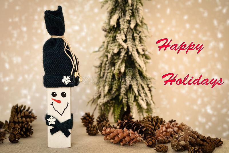 Wooden snowman and pine cones with Happy Holidays text. Decorated handmade wooden snowman and pine cones on the table in front of the Christmas tree and snowy stock photos