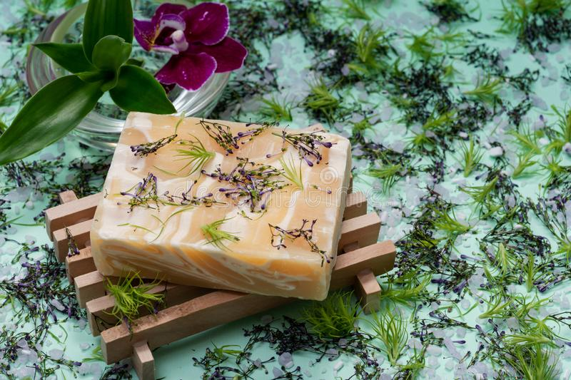 Wooden Soap Holder with Handmade Almond Scented Goat`s Milk Bar Soap decorated with Orchid Flower, Bamboo and  flower sprinkles. On green background stock photos