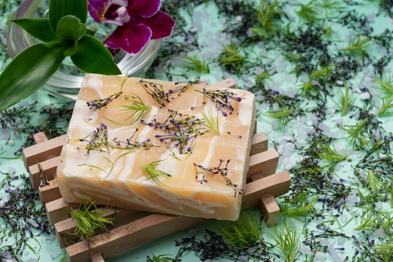 Wooden Soap Holder with Handmade Almond Scented Goat`s Milk Bar Soap decorated with Orchid Flower, Bamboo and  flower sprinkles. On green background stock images