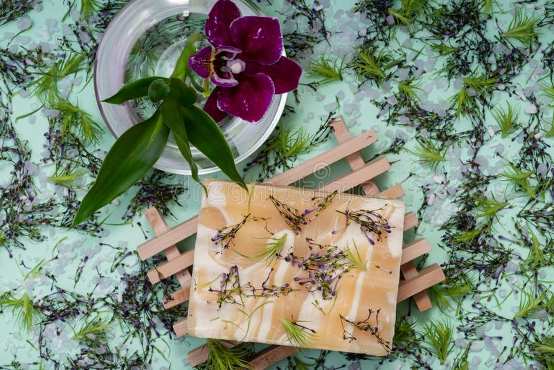 Wooden Soap Holder with Handmade Almond Scented Goat`s Milk Bar Soap decorated with Orchid Flower, Bamboo and  flower sprinkles. On green background stock photography