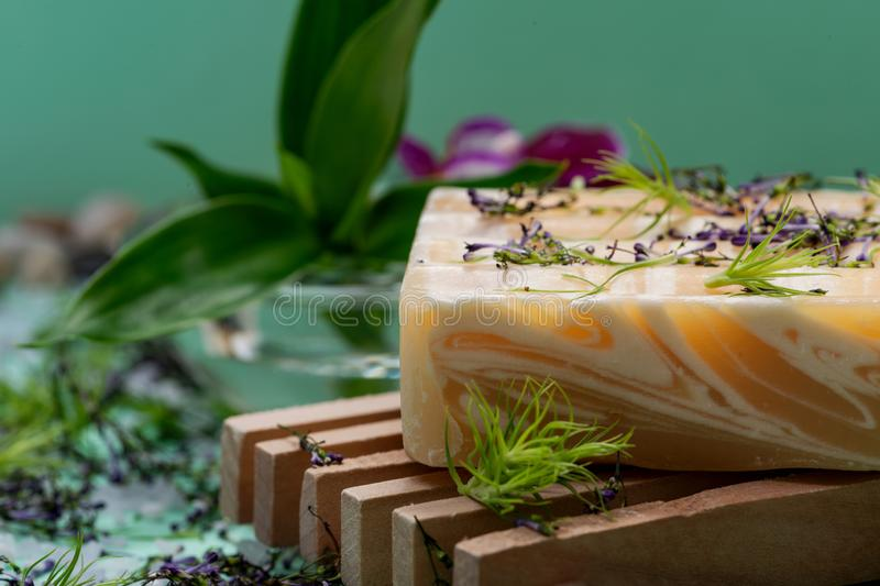 Wooden Soap Holder with Handmade Almond Scented Goat`s Milk Bar Soap decorated with Orchid Flower, Bamboo and  flower sprinkles. On green background royalty free stock photography