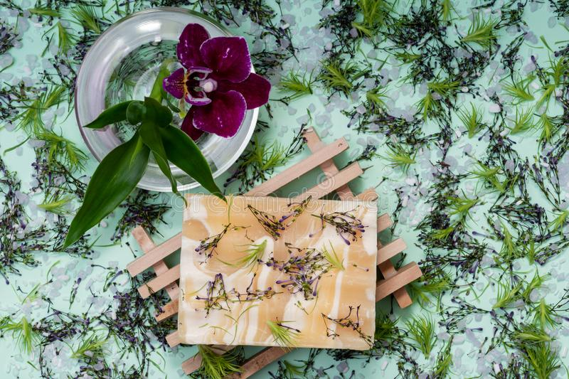 Wooden Soap Holder with Handmade Almond Scented Goat`s Milk Bar Soap decorated with Orchid Flower, Bamboo and  flower sprinkles. On green background royalty free stock photo