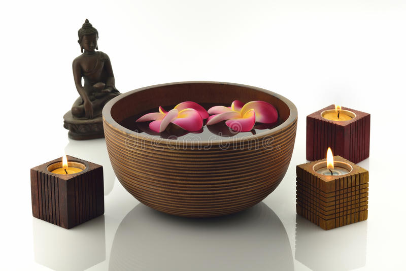 Wooden Spa Bowl on White Background with Buddha Statue,Candles and Flowers stock photography